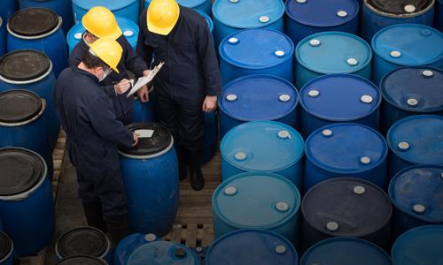 Workers Quality Checking Chemicals in Drums Ready to Supply