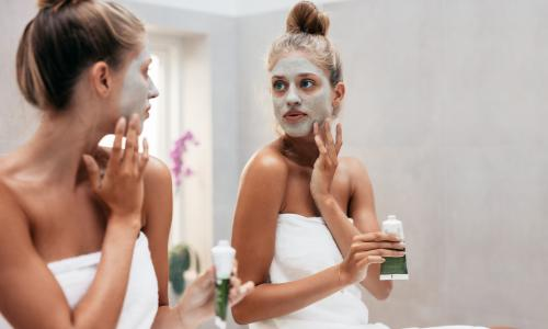 Woman looking in mirror with face mask